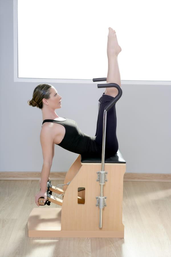 Aparelhos de Pilates e suas funções: aluno e instrutor praticando pilates.