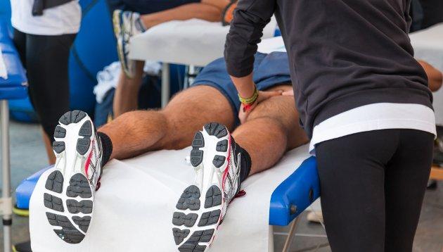 Benefícios da massagem desportiva: Homem recebendo massagem após prática de esportes