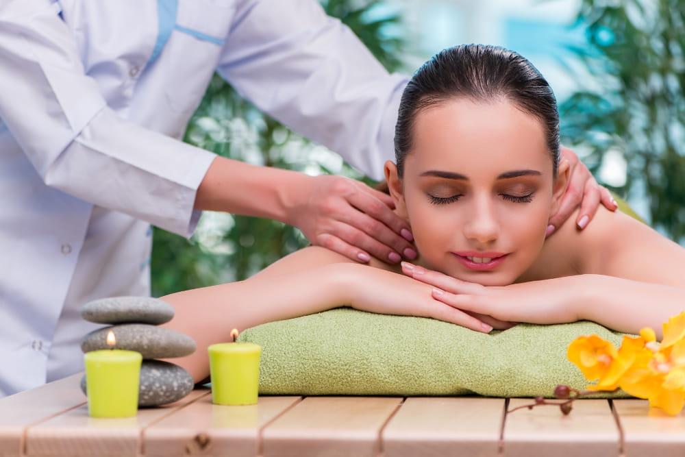 Benefícios da Massoterapia: Mulher jovem em sessão de massagem