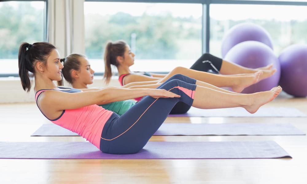 Benefícios do Pilates: mulheres deitadas na esteira esticando braços e pernas