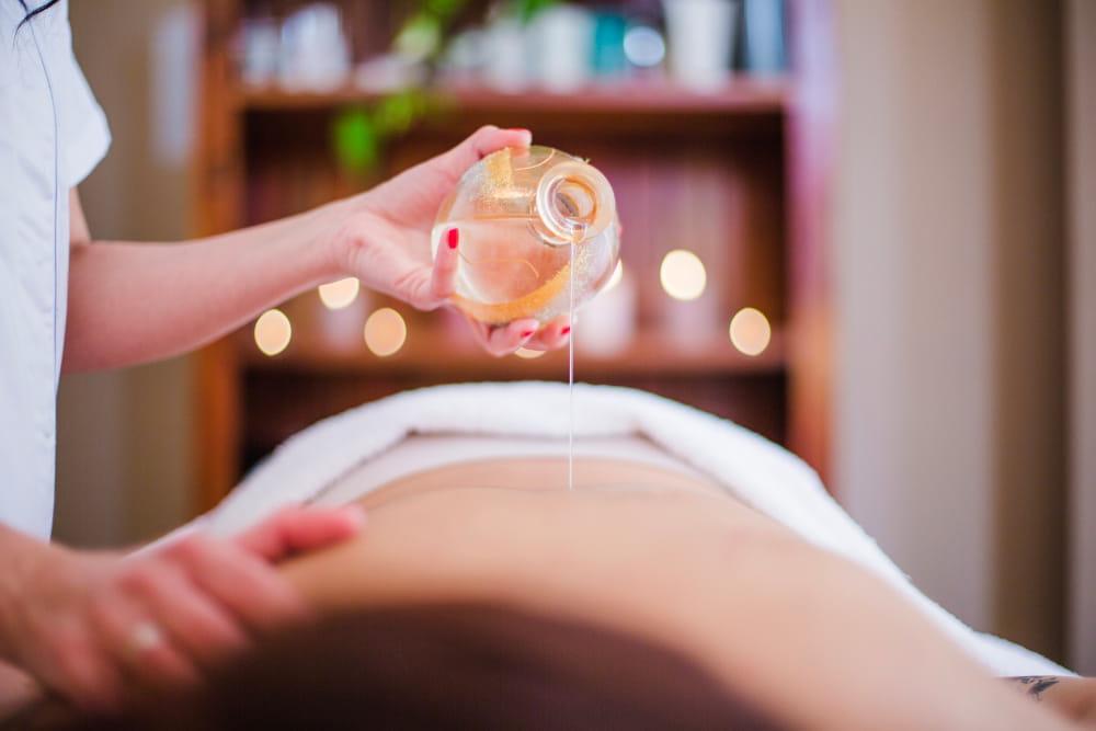 Benefícios dos Óleos Essenciais: Mulher em sessão de massagem com óleo essencial.
