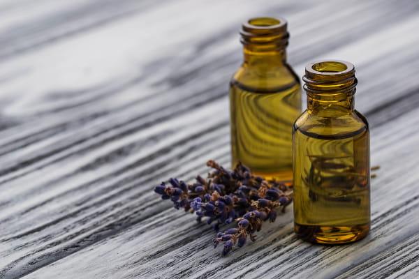 Benefícios dos Óleos Essenciais: Dois frascos de óleo essencial de lavanda abertos sobre uma madeira rústica.