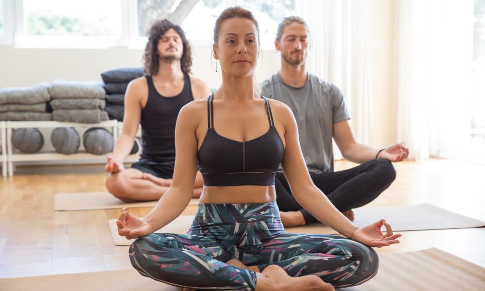 Como a meditação pode ajudar no stress: grupo de alunos em uma aula de yoga.