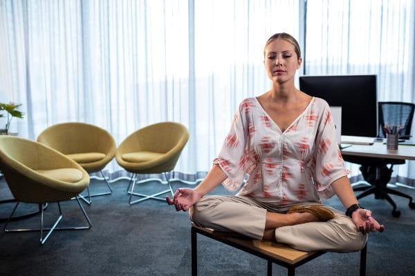 Como a meditação pode ajudar no stress: empresária meditando em seu escritório.