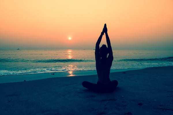 Fundamentos do Yoga: Ahimsa: mulher praticando yoga na praia.