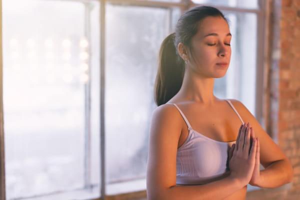 Fundamentos do Yoga: Satya: mulher em saudação Namastê.