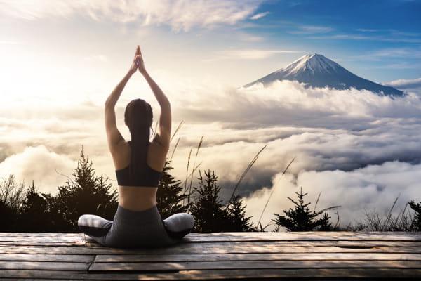 Jalaneti um processo de purificação através da Lota: mulher praticando meditação em frente a uma paisagem exuberante.