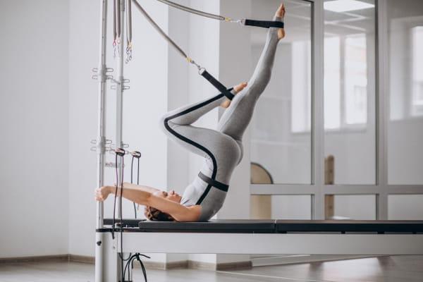 Pilates e Yoga: mulher em um aparelho praticando Pilates.