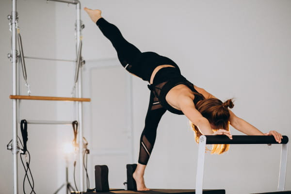 Pilates em Alphaville: Mulher praticando Pilates em aparelhos.