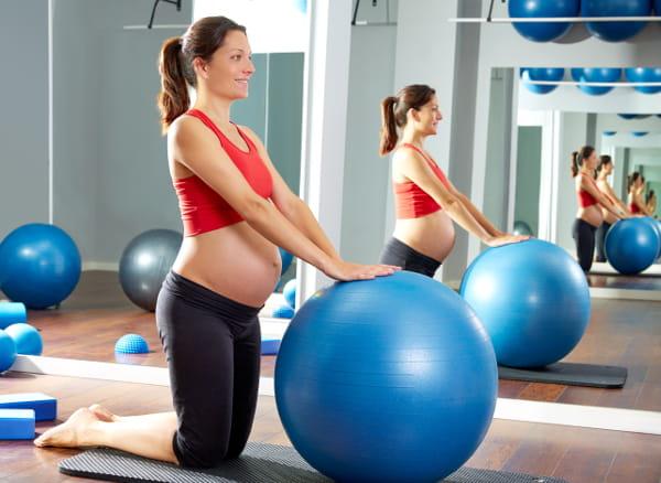 Pilates para Gestantes: mulher grávida praticando pilates com uma instrutora.