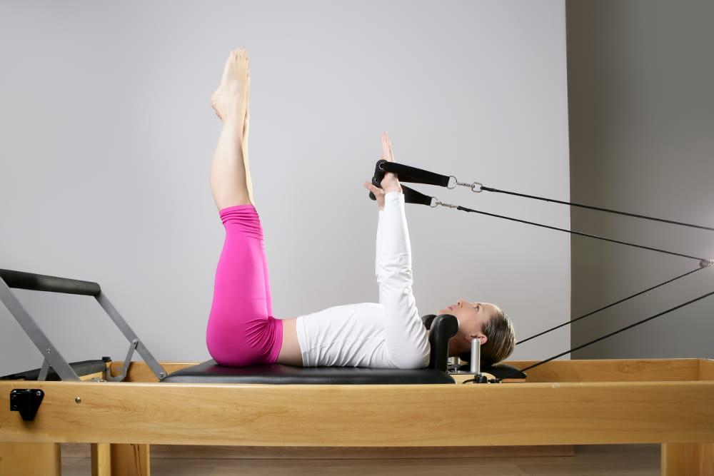Pilates reduz os efeitos da menopausa: mulher fortalecendo a musculatura com elásticos.