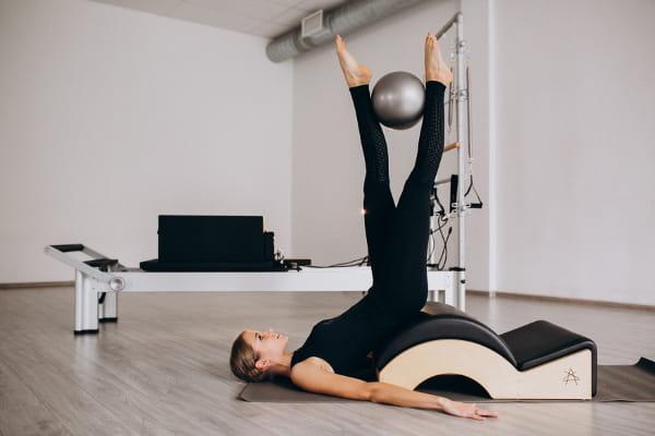 Pilates para mulheres: instrutora praticando pilates no solo com uma bola.