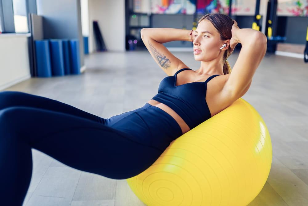 Pilates: seu pescoço agradece: mulher praticando Pilates sobre uma bola.