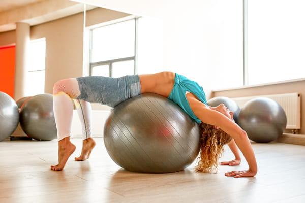 Pilates: uma turbinada em sua imunidade: mulher de costas sobre uma bola.