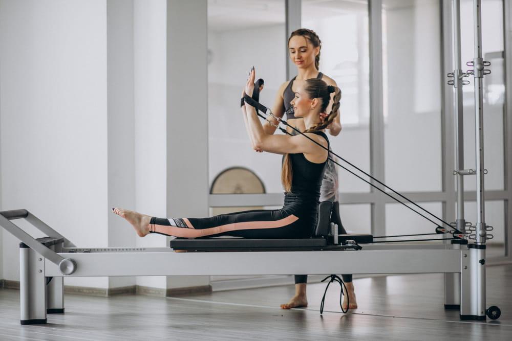 Precisão e controle no Pilates: mulher em uma posição de yoga com o sol ao fundo.