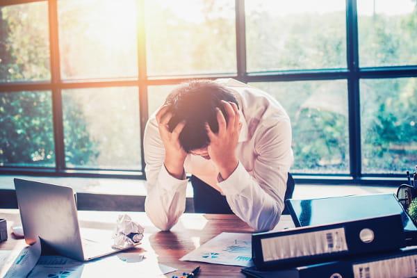 Síndrome de Burnout e as terapias naturais: homem com as mãos na cabeça sob forte stress.