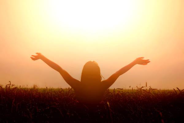 Terapia Barra de Access: mulher em um campo, com os braços abertos olhando para o sol.