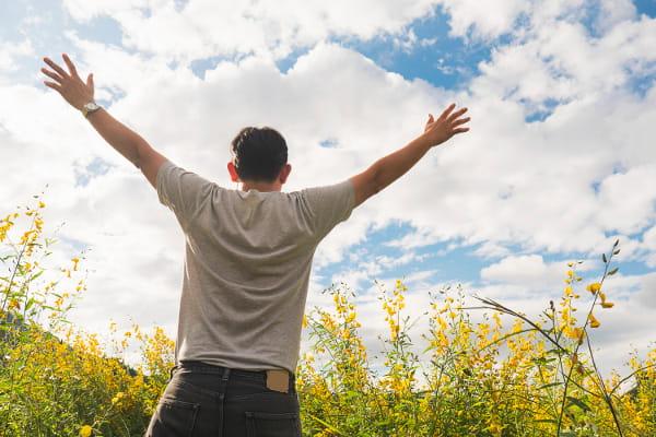 Thetahealing: homem em um campo florido com os braços abertos olhando para o céu