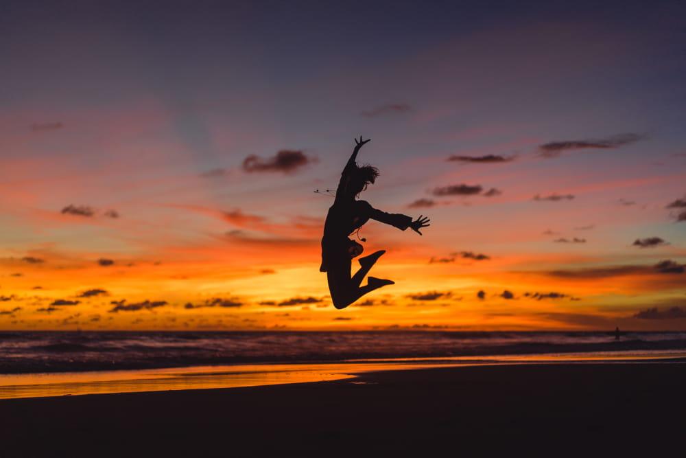 Thetahealing: o poder de criar a nossa realidade: mulher pulando na praia com sol se pondo.