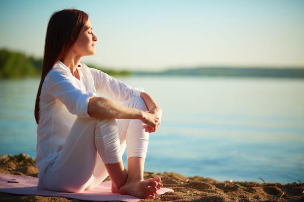 Thetahealing: o poder de criar a nossa realidade: mulher em um campo, com os braços abertos olhando para o sol.