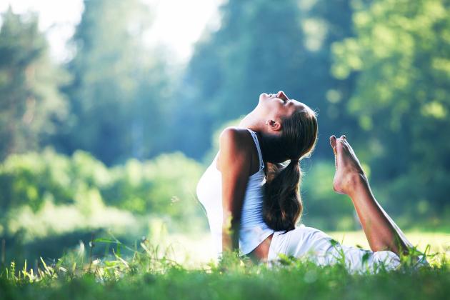 Mulher praticando Yoga na grama em um dia ensolarado