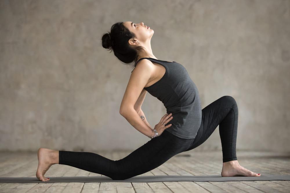Yoga - Um caminho para um corpo saudável e sem dores: mulher pulando na praia com sol se pondo.